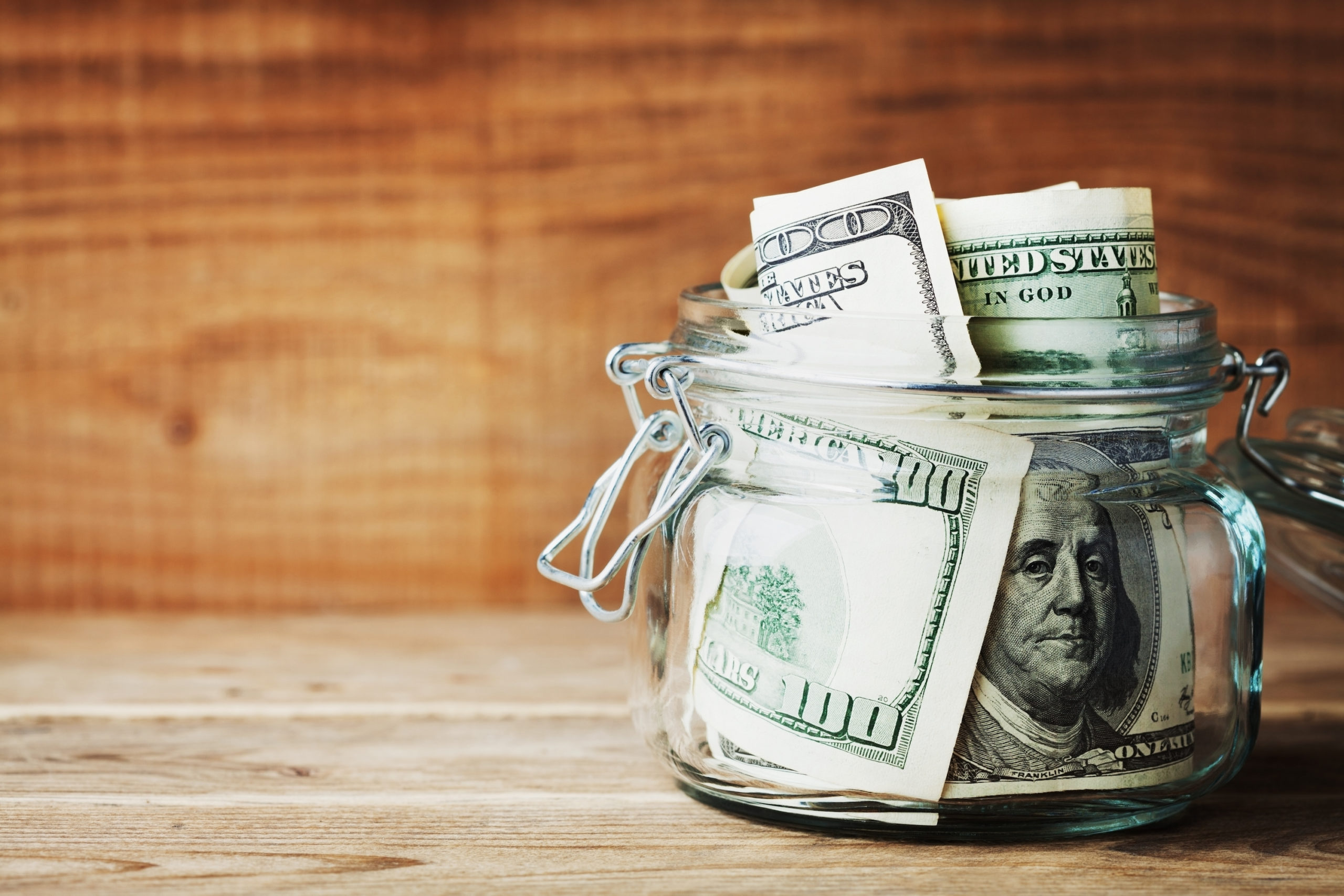 Collections attorney concept. Dollar bills in glass jar on wooden background. Saving money concept.