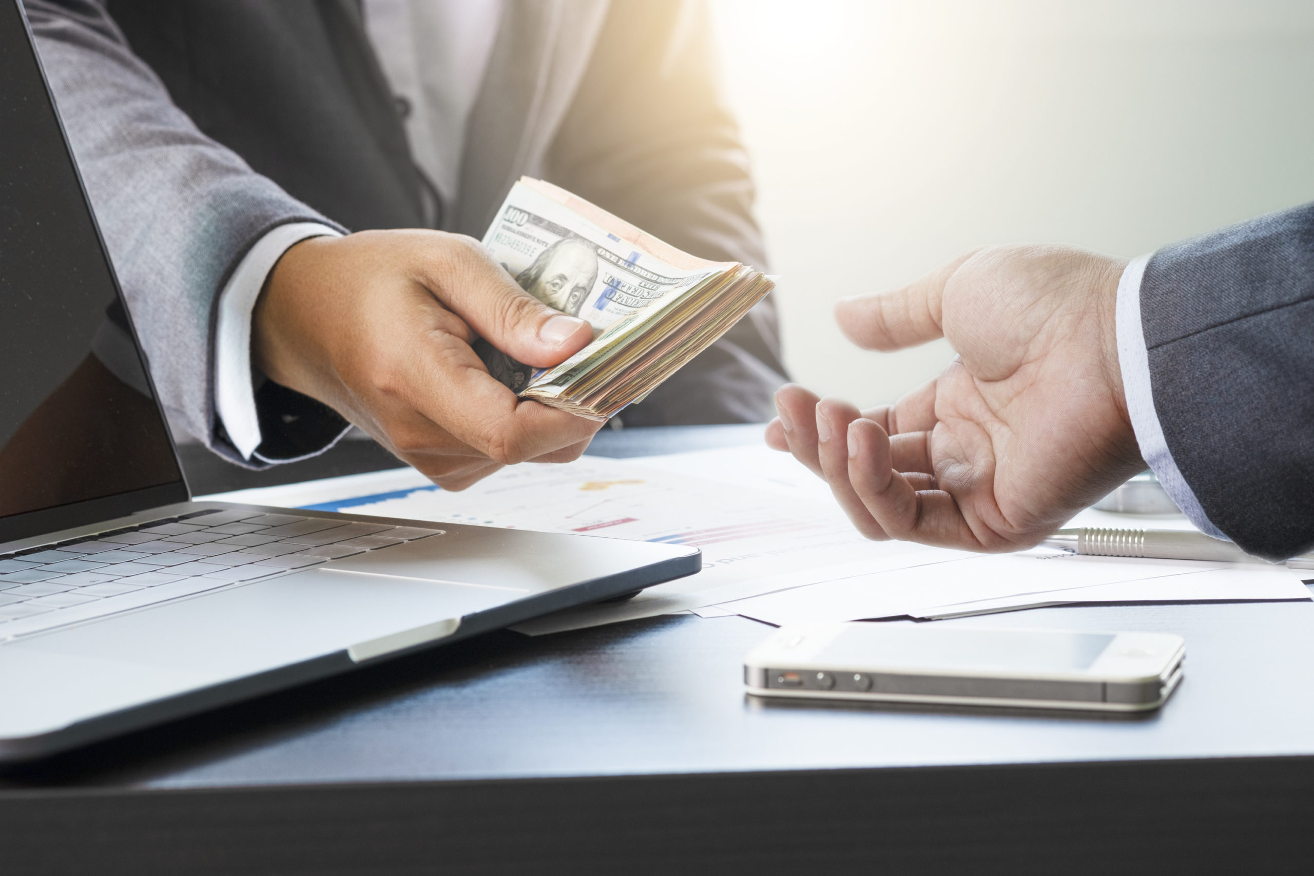 Collections attorney concept. Two businessmen give and take US dollar banknote .US dollar is main and popular currency of exchange in the world.Investment and payment concept.